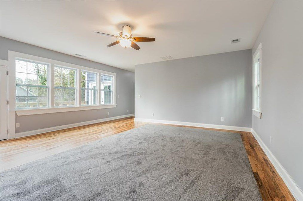 A huge gray room with a gray carpet atop the wood.