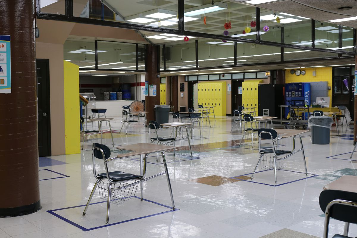 Desks for lunch are socially distanced in a school cafeteria.