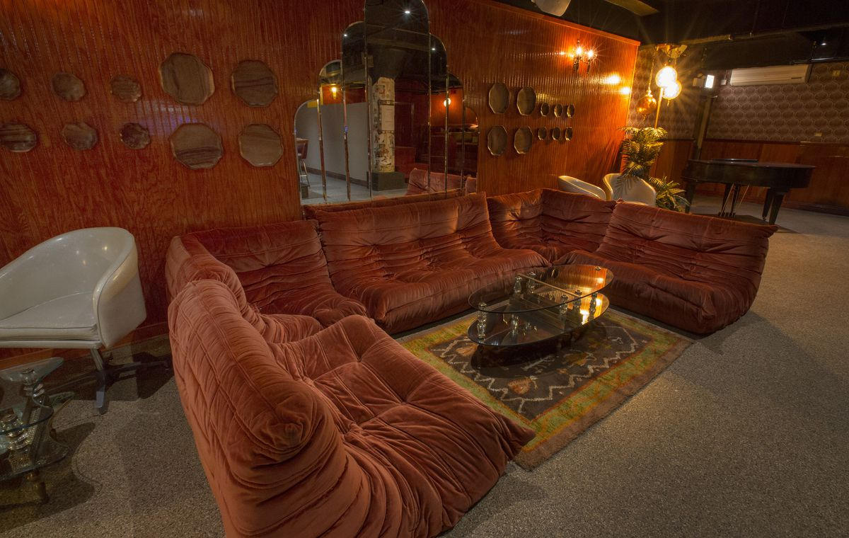 Couch seating with low tables in a basement bar.