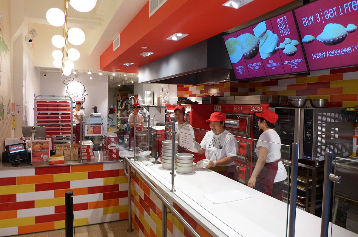 The inside of the restaurant shows several employees standing behind a glassed in counter wearing aprons and red hats, all women