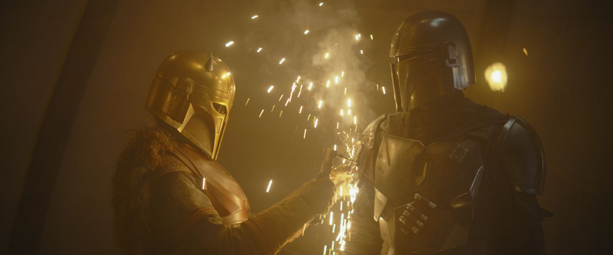 The Armorer spot-welding the Mandalorian's signet to his right pauldron.