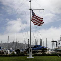 """In this photo taken Sunday April 15, 2012, a flag at the San Francisco Yacht Club hung at half staff in Belvedere, Calif. The search for four yacht crew members thrown from their boat during a weekend race off Northern California was indefinitely suspended, with the Coast Guard saying the """"window of survivability"""" had passed."""