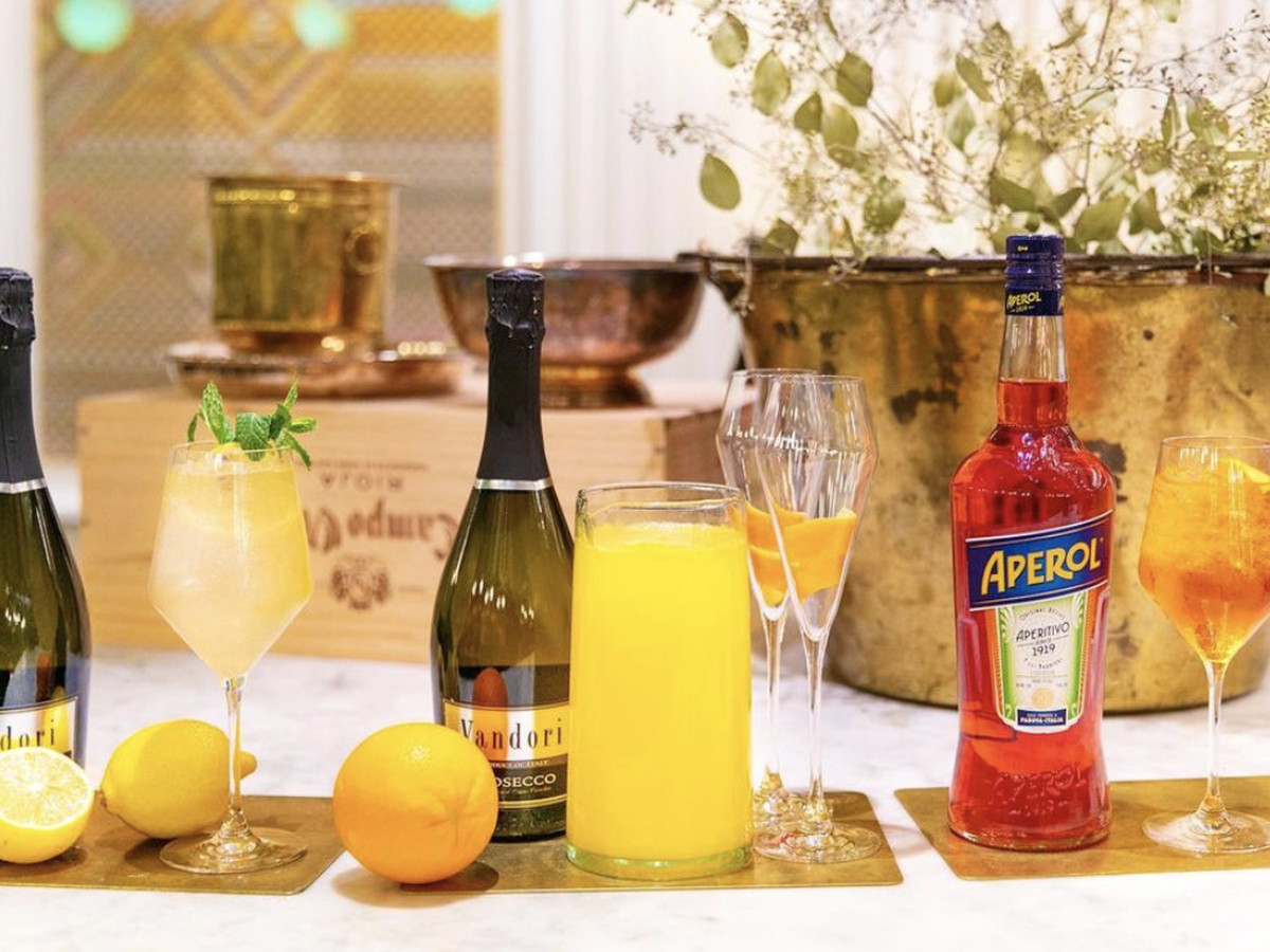 Bottles of champagne and one bottle of Aperol next to cocktail glasses on a counter festooned with floral arrangements, lemons and oranges