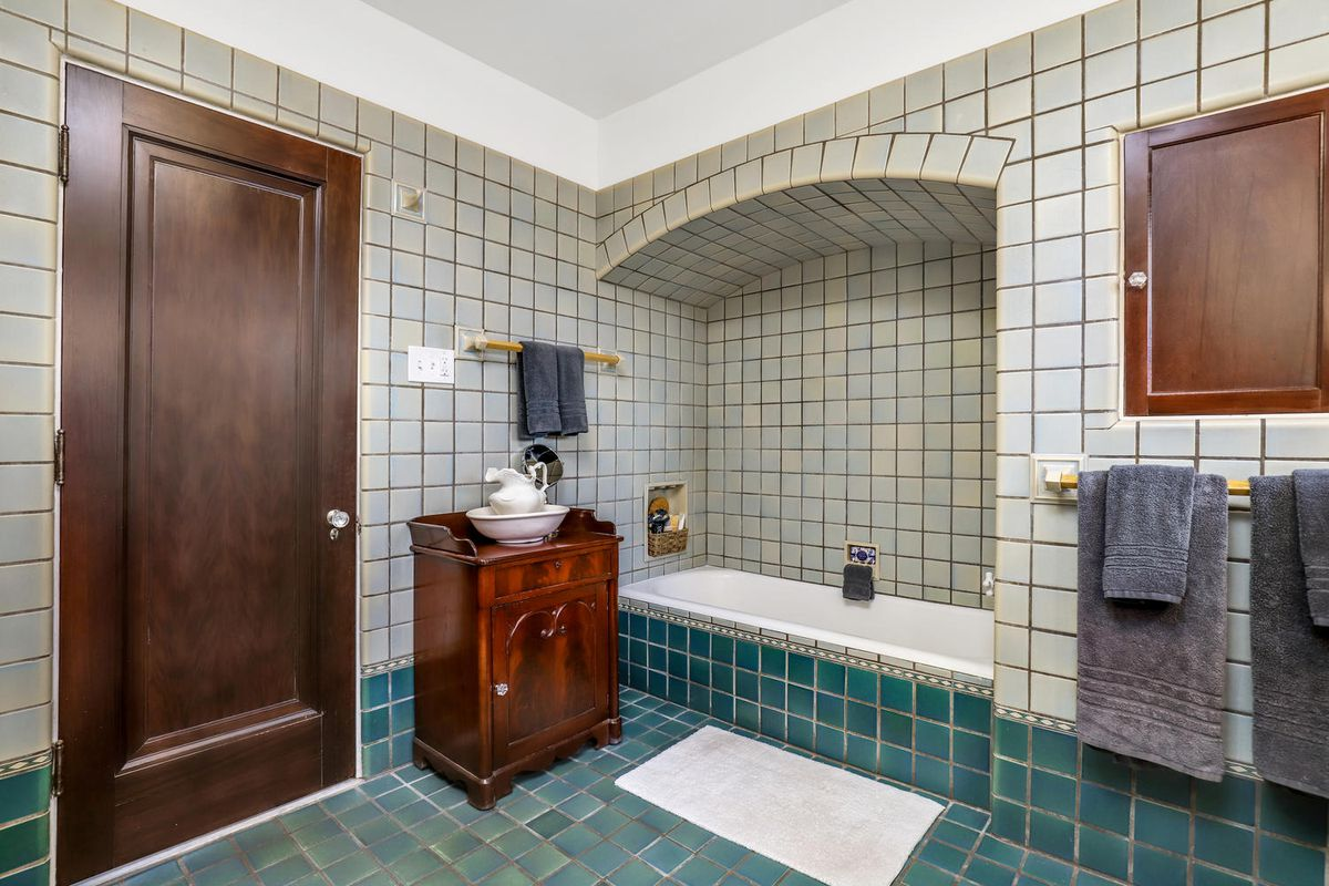 The floors and walls have dark and light green tiles. There's a tub set into the wall.