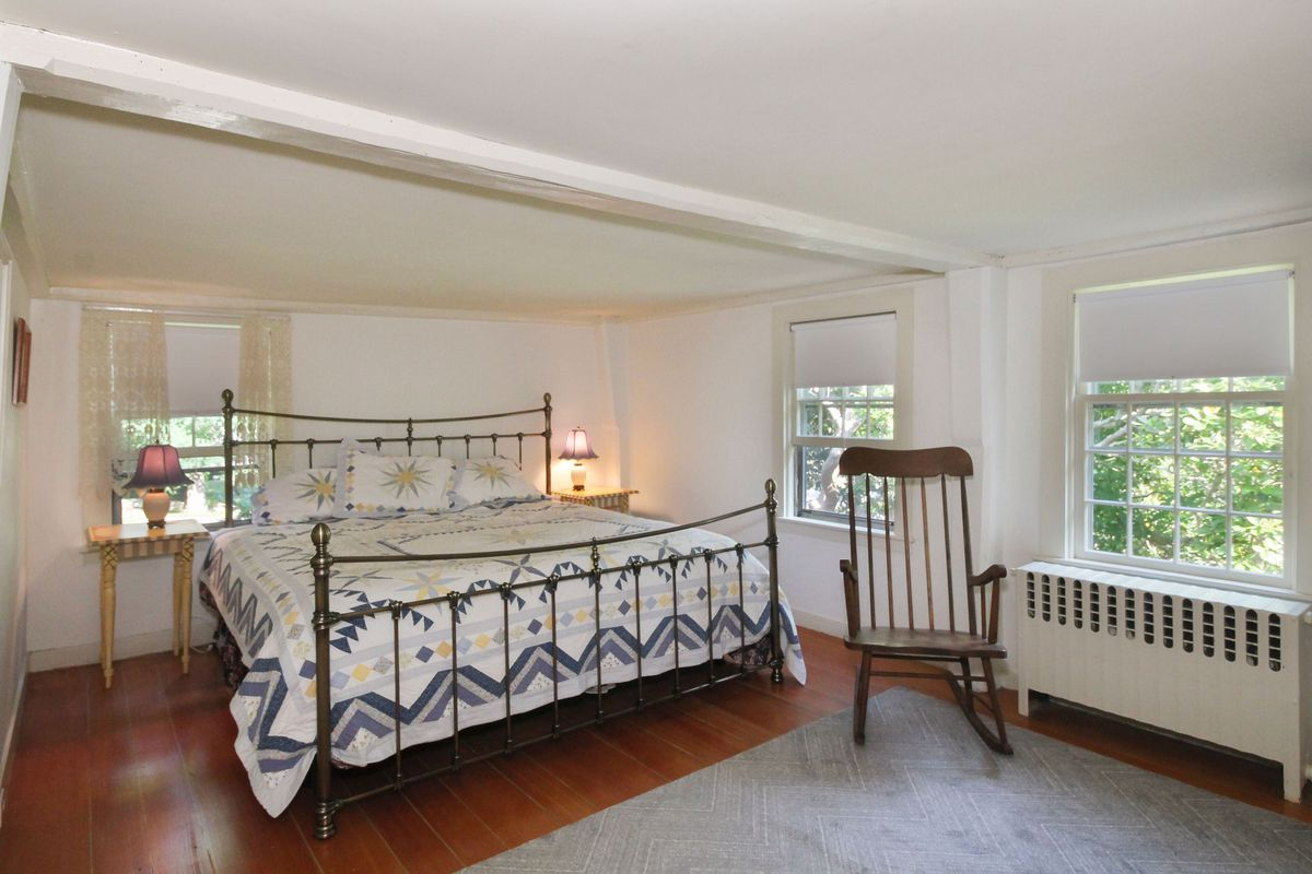 A colonial-style bedroom features a wrought-iron bed with blue and white quilt, a rocking chair, rug, and white walls.