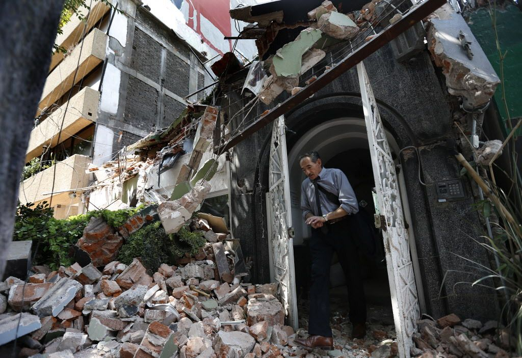 A man walks out of the door frame of a building that collapsed after an earthquake, in the Condesa neighborhood of Mexico City, Tuesday, Sept. 19, 2017. | Marco Ugarte/AP photo