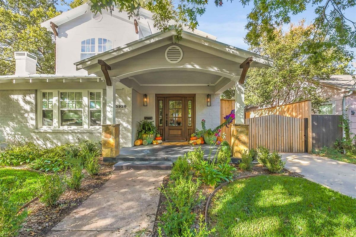 Craftsman-style home with large covered front porch entrance and small yard.