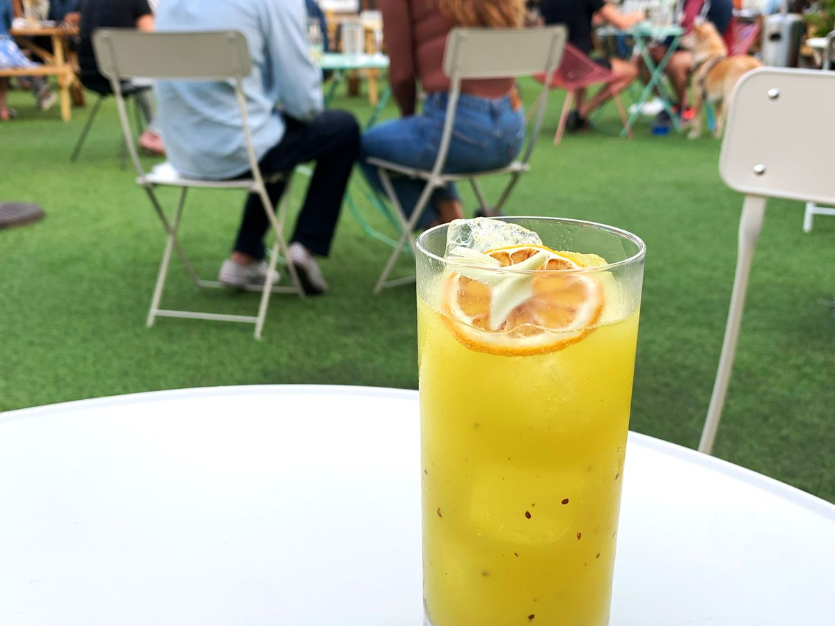 A yellow cocktail topped with a dried orange slice in an outdoor patio
