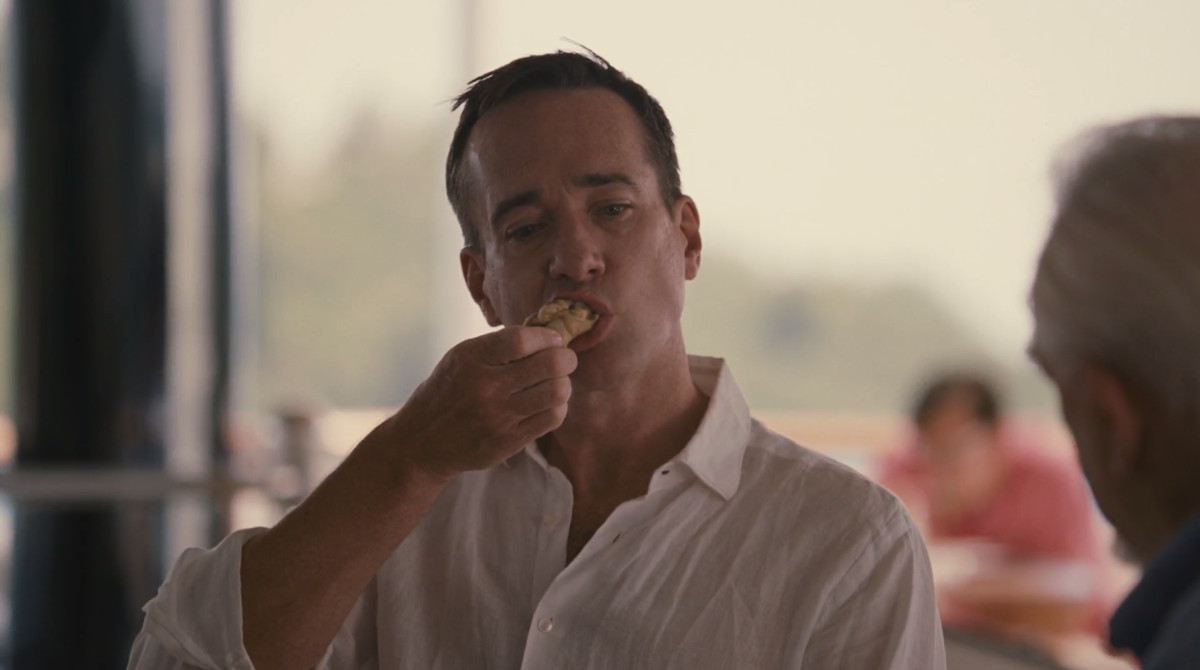 Succession screenshot: Tom eating a chicken wing in front of Logan.