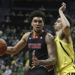 Utah's Timmy Allen, left, maneuvers against Oregon's Will Richardson during the second half of an NCAA college basketball game in Eugene, Ore., Sunday, Feb. 16, 2020.