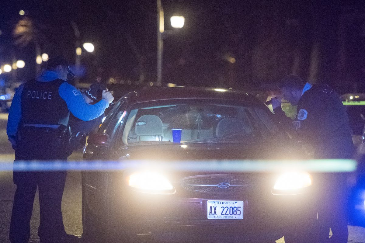 Chicago Police officers investigate the vehicle where two women were shot, Monday night in the 5400 block of West Glady's. This marks the final shooting of 2018 in Chicago. | Tyler LaRiviere/Sun-Times