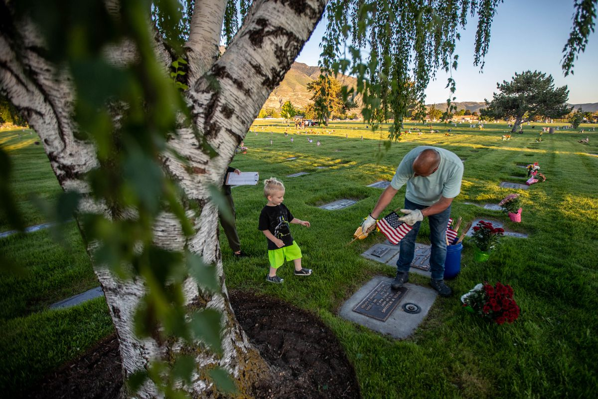 Rob Larkin, right, and his grandson Oliver, 2, left, place a flag on a grave at Larkin Sunset Gardens Cemetery in Sandy on Thursday, May 27, 2021. More than 200 youth volunteers from around the Salt Lake Valley honored military veterans for Memorial Day by placing 3,000 American flags on the graves of service members. In addition, they swept and polished headstones and helped beautify cemetery grounds.