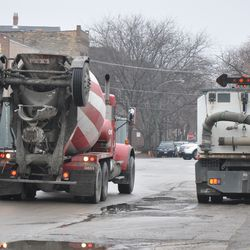 Due to the tight working quarters, this concrete mixing truck is backing up into the job site. The truck is traveling east down Waveland as the street sweeping truck moves aside