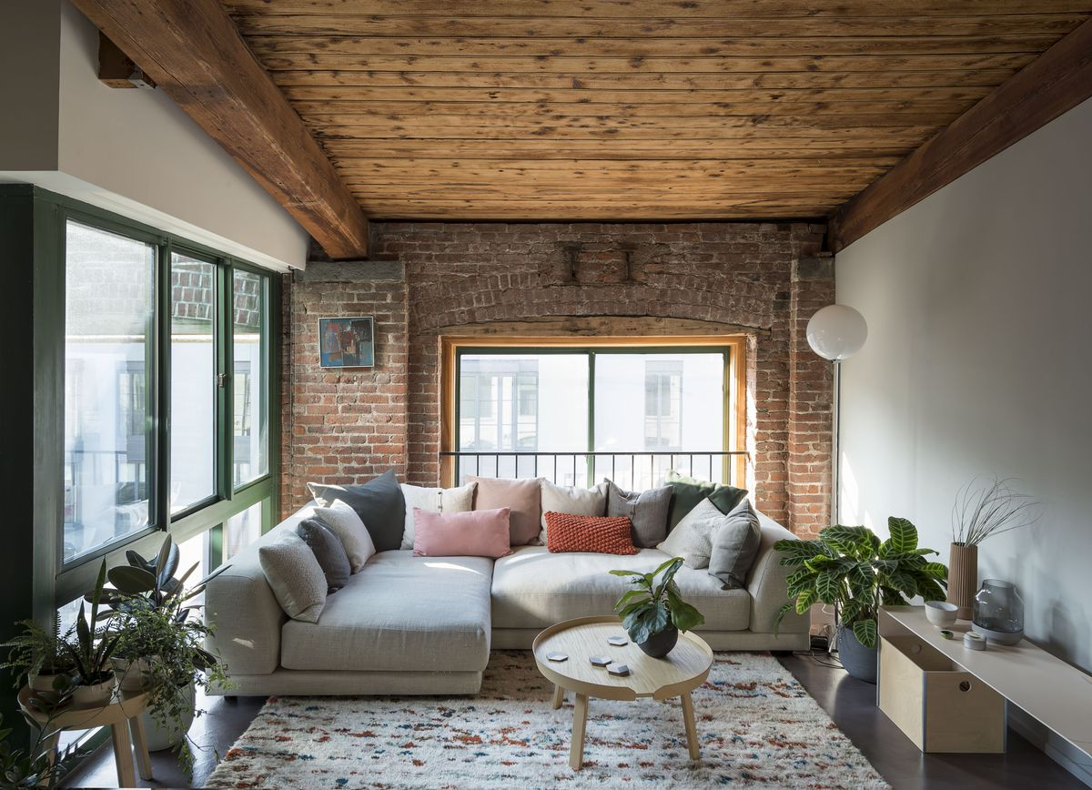A living room with a wood ceiling, concrete floors, and green-framed windows.