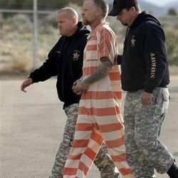 """Sanpete Sheriff's Officers escort Troy James Knapp, 45, to the Sanpete County Jail Tuesday, April 2, 2013, in Manti, Utah. Authorities on Tuesday captured Knapp, an elusive survivalist who is suspected of burglarizing Utah cabins and leaving some covered with threats and bullet holes — ending a saga that began six years ago and drew in police and residents around the state. Knapp, dubbed the """"Mountain Man"""" by cabin owners, was taken into custody in the snowy mountains outside of Ferron in central Utah after firing several shots at officers in a helicopter, authorities said. (AP Photo/Rick Bowmer)"""