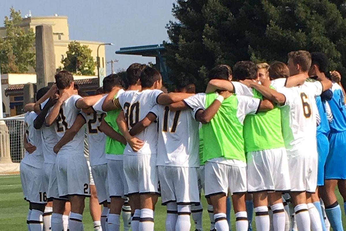 Cal men's soccer team huddles on field before a match