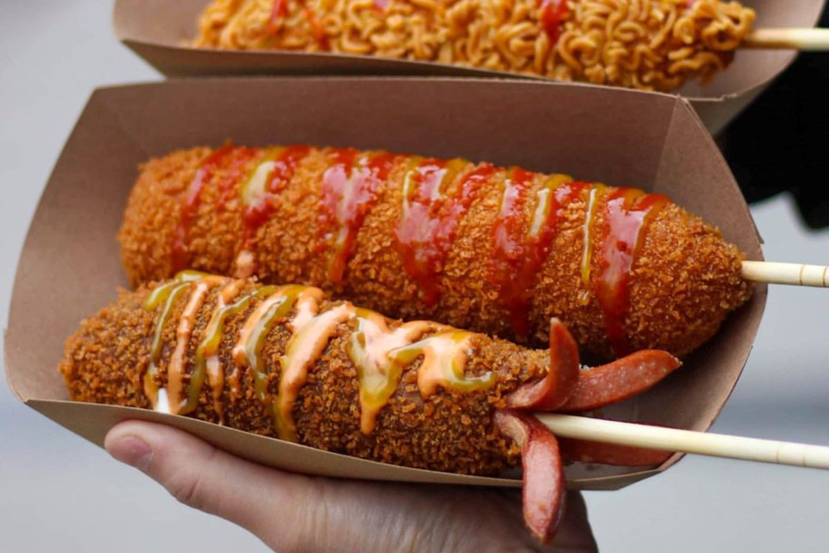 A hand holds two containers filled with corndogs which have been fried in pancake batter and slathered with ketchup and mustard