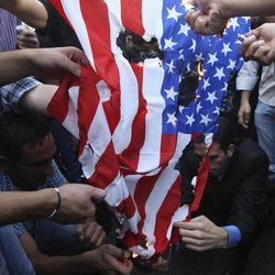 Palestinians burn a U.S. flag during a protest as part of widespread anger across the Muslim world about a film ridiculing Islam's Prophet Muhammad in the West Bank city of Nablus, Friday, Sept.14, 2012.