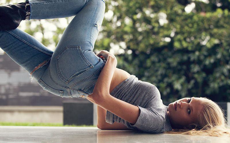GRLFRND lookbook image with model posing in distressed skinny blue jeans