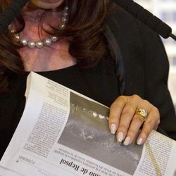 Argentina's President Cristina Fernandez holds a copy of the Spanish newspaper El Pais at Government House where she announced a bill to nationalize Spain's controlled oil company YPF, in Buenos Aires, Argentina, Monday April 16, 2012. Fernandez said in an address to the country that the measure sent to congress on Monday is aimed at recovering the nation's sovereignty over its hydrocarbon resources. The newspaper's headline and subhead read in Spanish: Repsol's Argentine springboard; YPF, cost 13.000 million euros, took the Spanish oil company to the height of the crude business and it represents a third of it's profit.