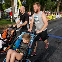 Lon Jenkins, with granddaughter Lottie Mosdell, 8 months, in a stroller, left, and Mike Mosdell, with daughter Greta Mosdell, 5, in a stroller, finish the Deseret News 10K at Liberty Park in Salt Lake City on Friday, July 23, 2021.