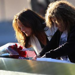 Tina Grazioso, left, looks at the name of her husband, John Grazioso, at the World Trade Center Memorial, who died in the attacks at the World Trade Center, during the 11th anniversary observance, in New York, Tuesday Sep. 11, 2012. At right is John Grazioso's sister Carolee Azzarello.