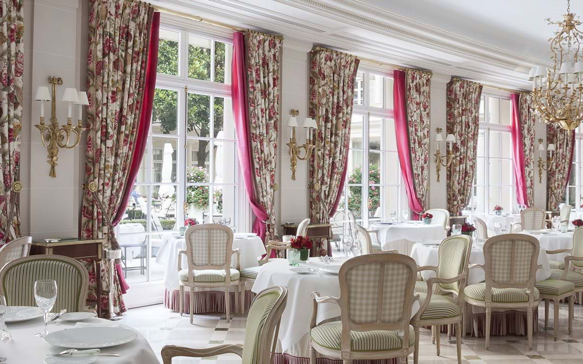 A formal dining room almost all in white, with heavy floral curtains, ornate lighting, and patio seating visible through large French doors