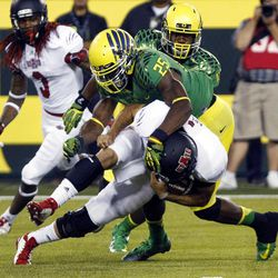 Arkansas State quarterback Ryan Aplin, bottom, is wrapped up by Oregon defender Boseko Lokombo during the first half of their college football game in Eugene, Ore., Saturday, Sept. 1, 2012.