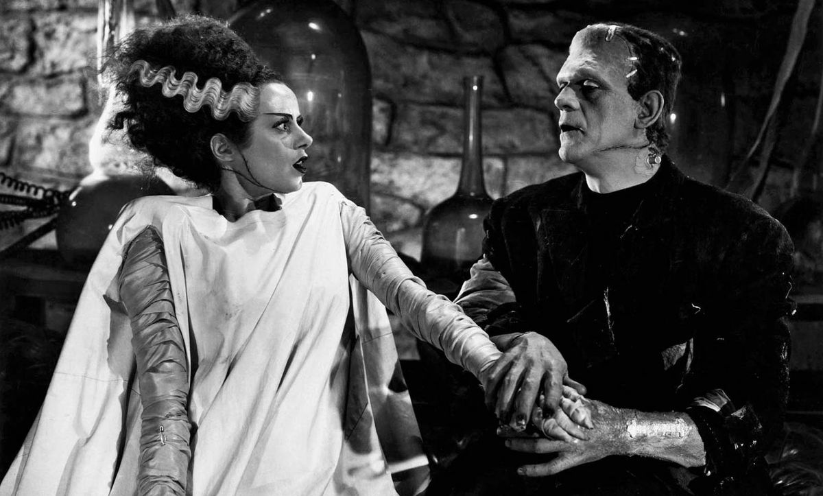 In a still from The Bride of Frankenstein, Boris Karloff as the monster holds the hand of a horrified-looking Elsa Lanchester as his newly created mate.