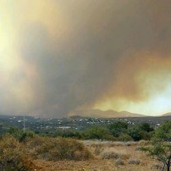 In this photo provided by Jill Baker, a forest fire burns through a rugged section of Arizona on Wednesday, June 28, 2017, near the town of Mayer, Ariz. The wildfire burning through a dense Arizona forest has forced thousands of people from their homes, closed a major road and created a huge plume of smoke over the same area devastated by a blaze that killed 19 firefighters four years ago.