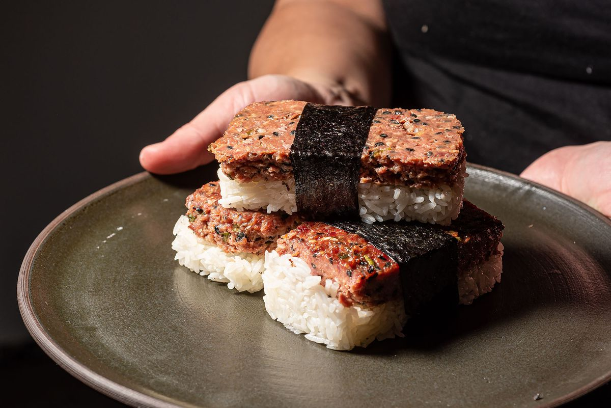 A tray of three musubi held up by hands.