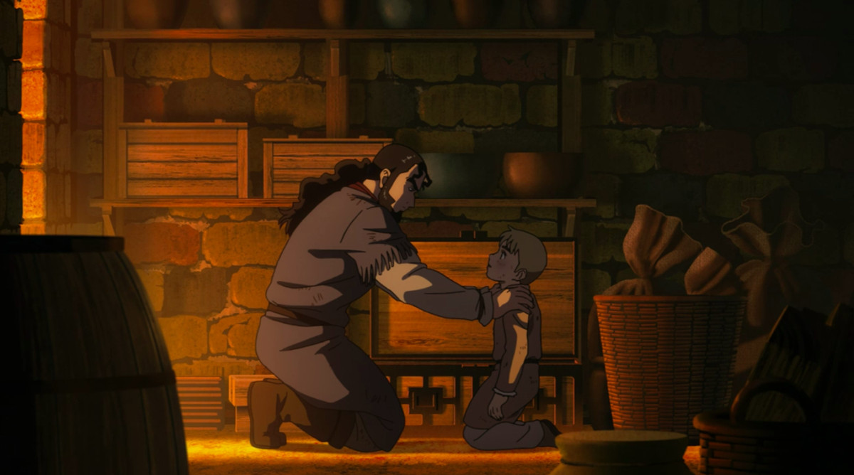 A father kneels with his hands on his son's shoulders. They are in a log cabin.