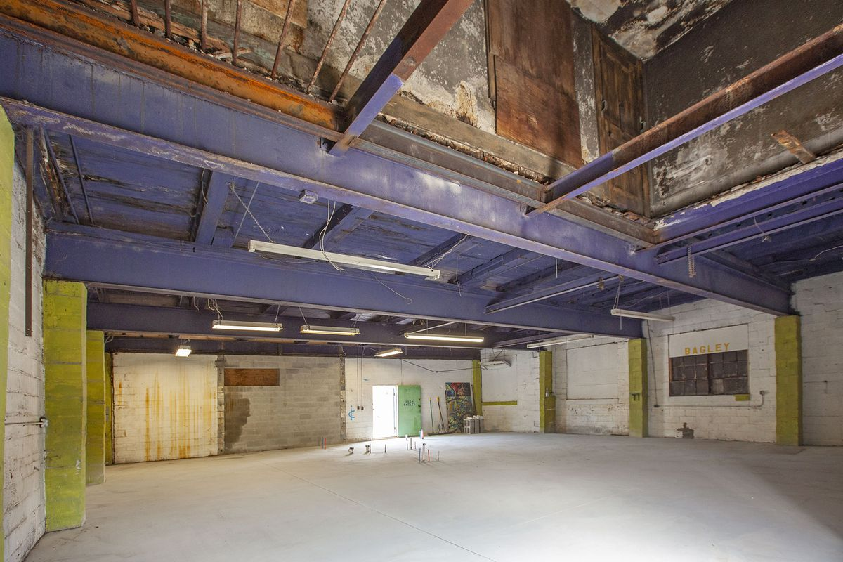 View of the same room but from a different angle. There's an empty spot in the ceiling, possibly where cars were once raised.
