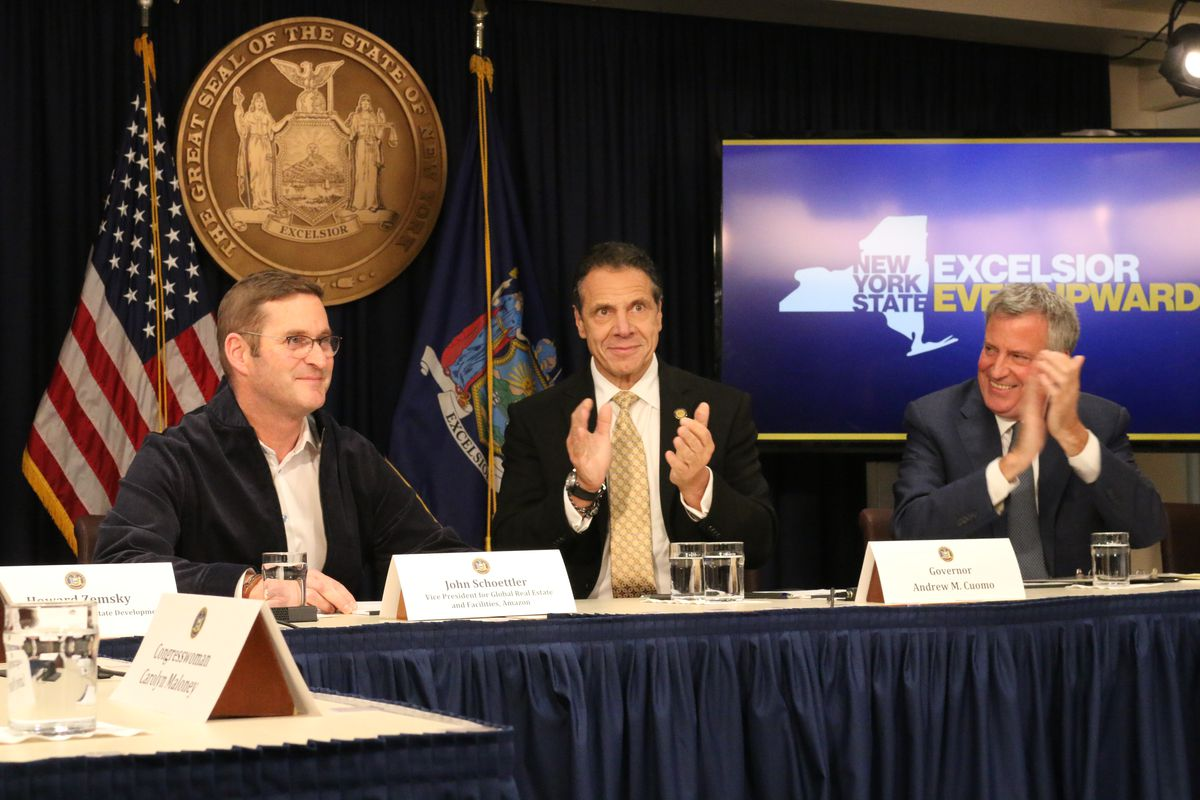 John Schoettler, Amazon's vice president of global real estate and facilities, (left) sits with Gov. Andrew Cuomo and Mayor Bill de Blasio at a press conference about Amazon's announcement to open part of its new headquarters in Long Island City.