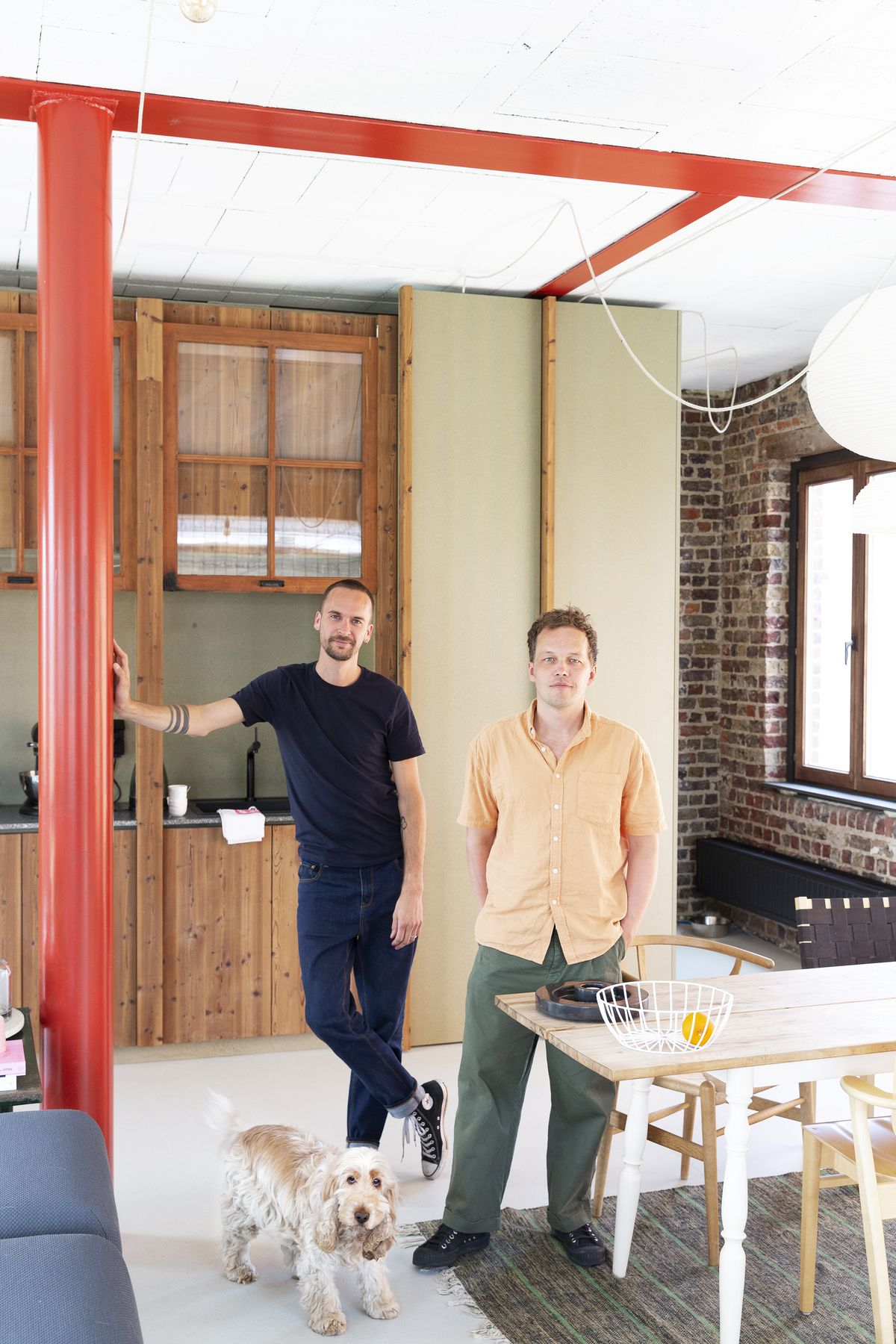The homeowners, two men, stand in a room with a tan and white dog. There is a wooden table and a red column. On the far wall is a sink and wooden cabinetry.