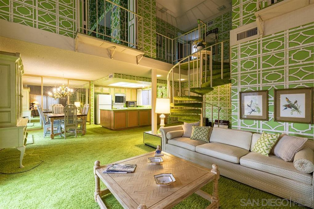 Living room with a green patterned walls, solid green carpet, and beige sofa and coffee table.