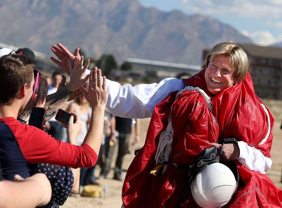 "Overstock employees high five CEO Patrick Byrne after he parachuted into the groundbreaking ceremony of the company's new corporate campus, referred to as the ""Peace Coliseum"", in Midvale on Friday, Oct. 10, 2014."