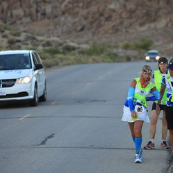 Linda Quirk of Jacksonville, Florida is bent over in back pain, a common condition among the athletes in the event after running 100 miles, as she makes the final ascent up Whitney Portal Road to the finish of the AdventurCORPS Badwater 135