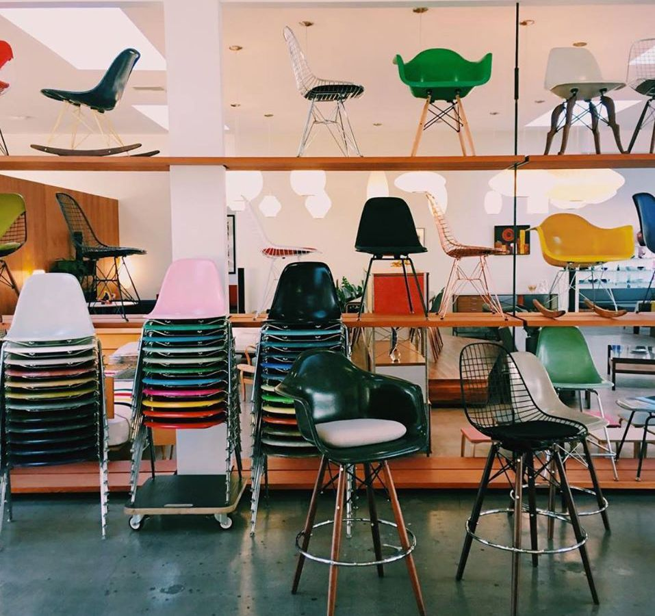 Many chairs are stacked on top of each other. There are also assorted chairs arranged on shelves on display. The floor is emerald green.