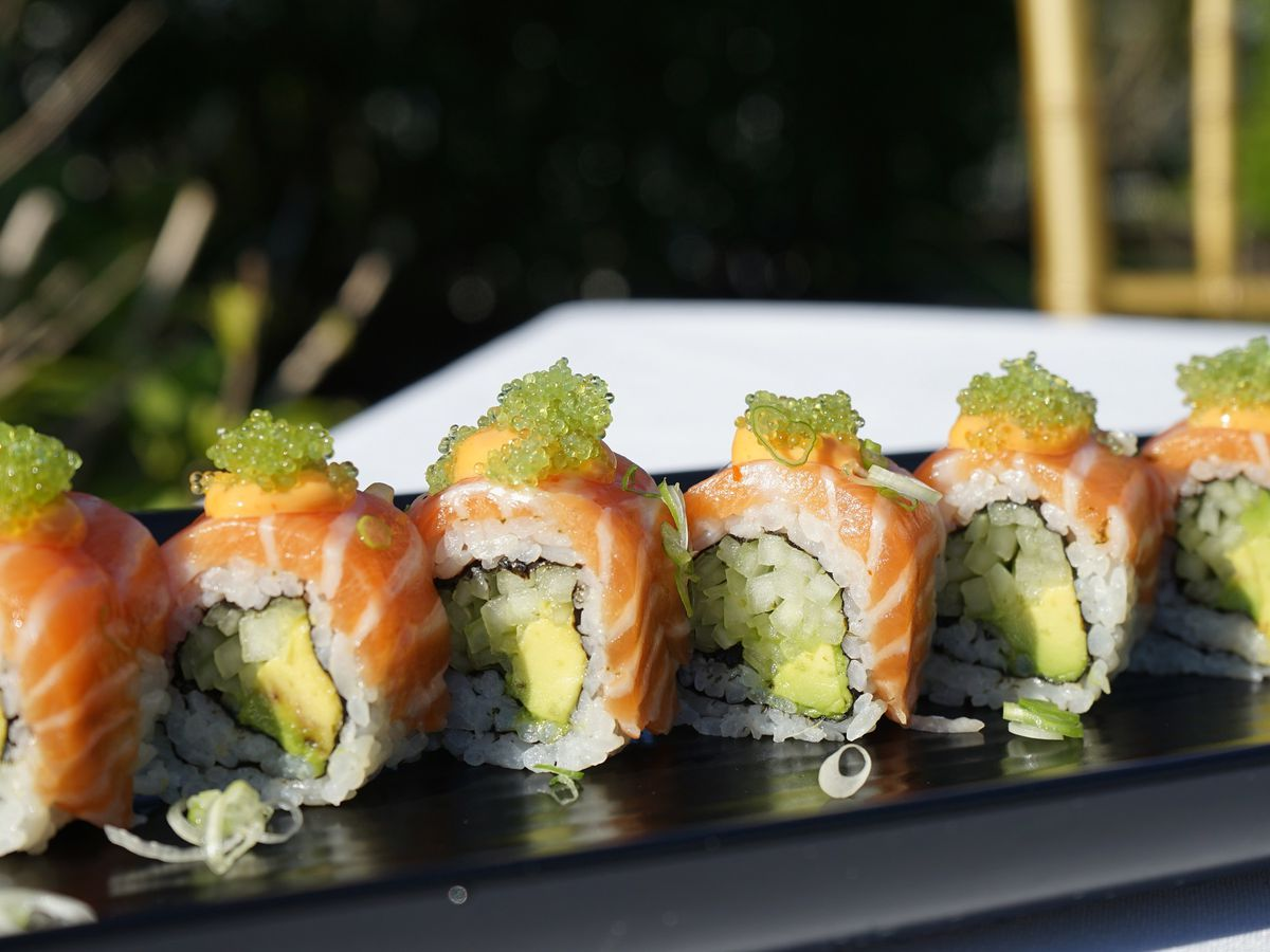 A sliced sushi roll on a dark platter. The roll has avocado in the middle and strips of salmon and roe piled on top.