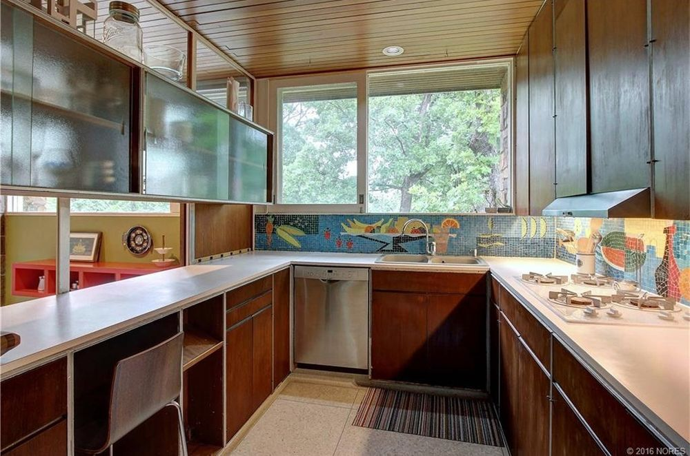 A midcentury modern kitchen. There is wooden cabinetry, colorful decorative mosaics, a wooden ceiling, and a linoleum floor.