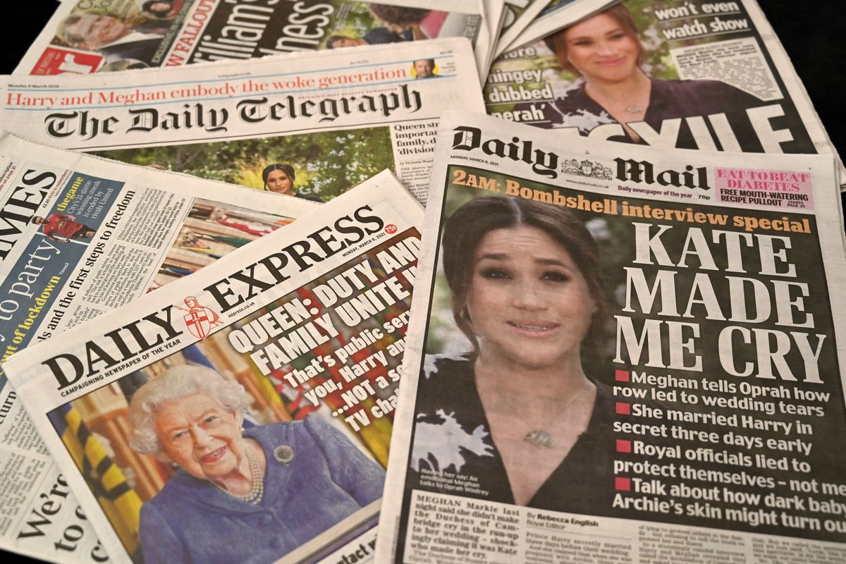 Tabloid covers of Meghan Markle and the Queen lie scattered.