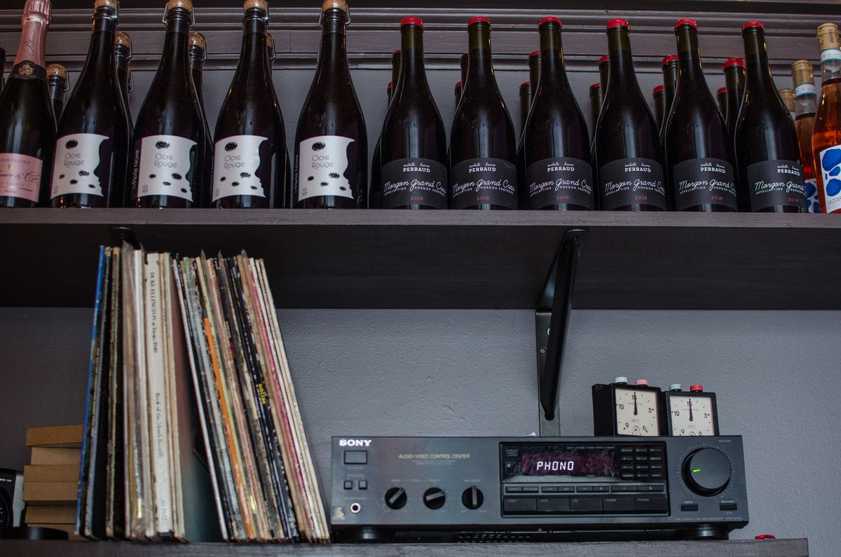 Records are lined up next to a stereo on a shelf. Above, on another shelf, are wine bottles. The shelves and wall behind them are dark gray.