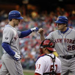New York Mets' Jason Bay, left, and Daniel Murphy, right, celebrate after Bay's two-run home run in the first inning of a baseball game against the Philadelphia Phillies, Friday, April 13, 2012, in Philadelphia. Phillies catcher Carlos Ruiz, center, looks on.