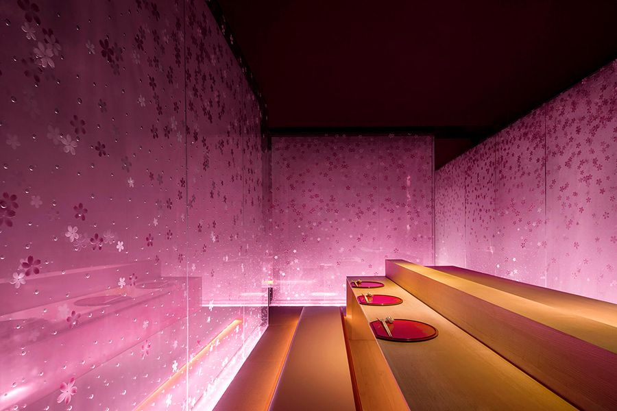 A sushi restaurant with glowing pink walls and wooden tables. The walls are decorated with a sakura pattern.