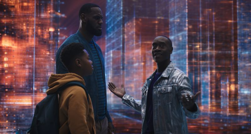 """LeBron James, Cedric Joe as his son Dom, and Don Cheadle as """"Al G. Rhythm"""" in Space Jam: A New Legacy. They are surrounded by flashing lights."""