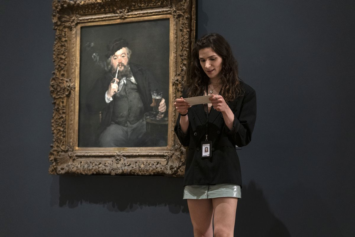 Simone beside a painting in an art museum.