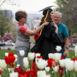 """Heidi Kulicke's mother, Lynn Kulicke, helps with her graduation gown while her dad, Allen Kulicke, watches on the University of Utah's campus before a virtual commencement ceremony amid the COVID-19 pandemic on Thursday, April 30, 2020. Lynn earned a master's in social work. """"It's a strange year,"""" she said."""