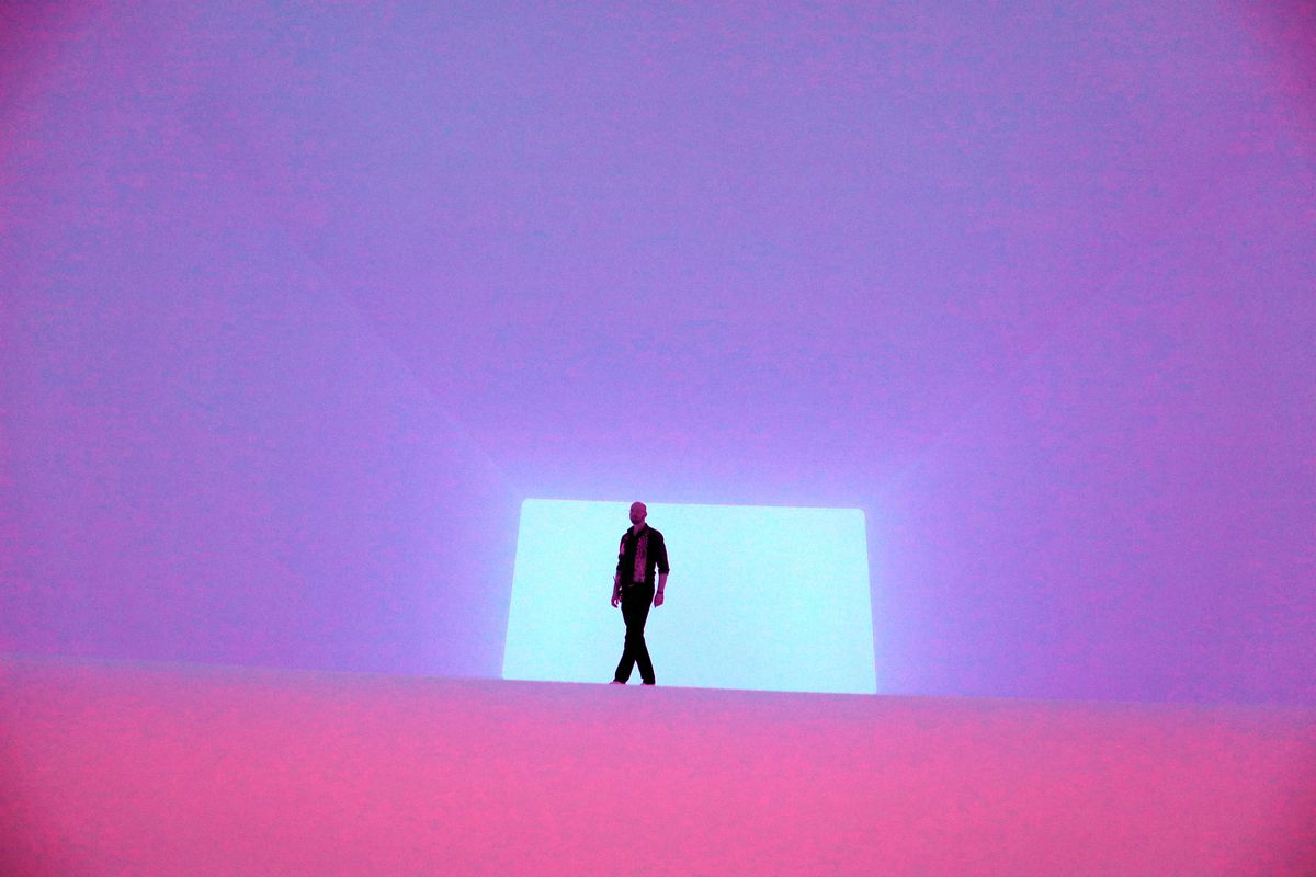A figure is silhouetted against a green rectangle in a field of purple and pink light.