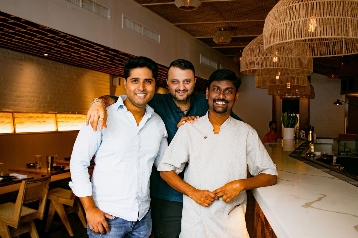 Three men stand next to Semma's bar, smiling at the camera.